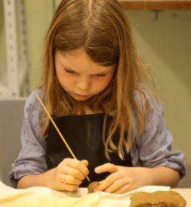 Olivia er koncentreret om at lave et pindsvin i ler.
