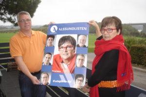 Med Alssundbroen i baggrunden præsenterer byrådskandidaterne Johnny Søndergaard og Karen Damm Alssundlistens team-inspirerede plakat.