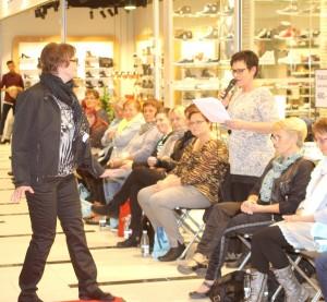 Modellen kigger på butikscehf Marion Lippert, der venligt og bestemt guider gæster og modeller gennem aftenen.