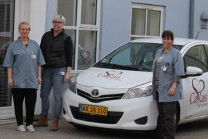 Jane Thøisen sammen med sine arbejdsgivere og den splinternye firmabil.