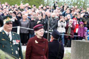 Dronningen og Prinsgemalen lægger en krans ved en af fællesgravene.
