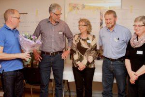 Claus Klaris står med blomster til fire borgere fra Årets Landsby.