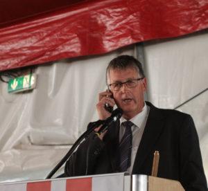 Erik Lauritzen tager telefonen midt i sin taletid.