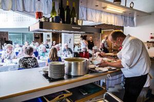 Kokken har travlt med at anrette de mange tallerkener.