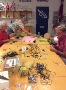 De frivillige gør sig umage med at lave halskæder, som skal sælges lørdag.