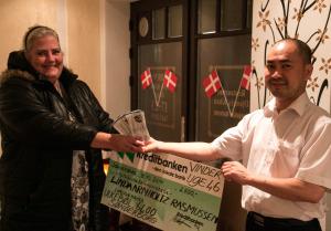 Linda Arnholtz Rasmussen får omgående 2500 kroner i hånden, så den store vindercheck kan blive hængt op i restauranten. <div class=