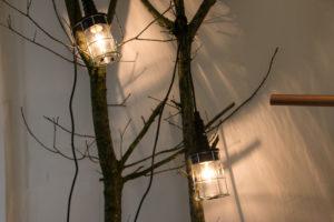 Stil grene ind i stuen og hæng nogle gamle håndværkerlamper i dem.