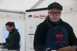 Claus Holm underholder mens fru Anne arbejder i baggrunden.