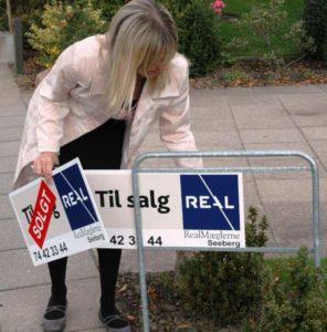 Dorthe Seeberg sætter et SOLGT-skilt op. Foto: Ole Kæhler