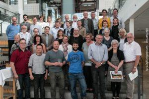 Skulpturmodtagere, kunstnere og værtsfamilier samlet i Café Alsion.