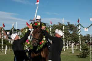 Johannes Brink får vinderkransen på sin hest.