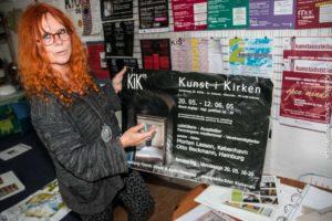 Karin Baum viser plakaten fra en af rigtigt mange udstillinger.