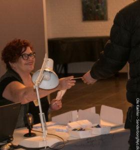 Lis Augustenborg udruster en vælger med stemmeseddel.