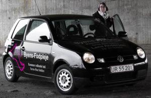 Lena Andersen med den bil, der er ramme om hendes firma. <div class=